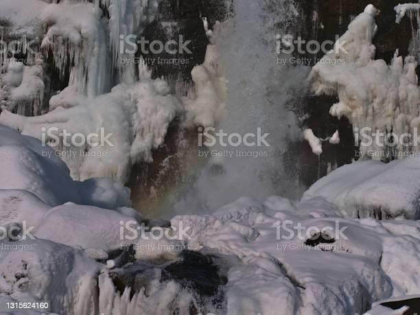 Photo of Stunning closeup view of Öxarárfoss cascade in rocky Almannagjá canyon in Þingvellir national park, part of Golden Circle, Iceland, in winter season with small rainbow, snow and icicles.