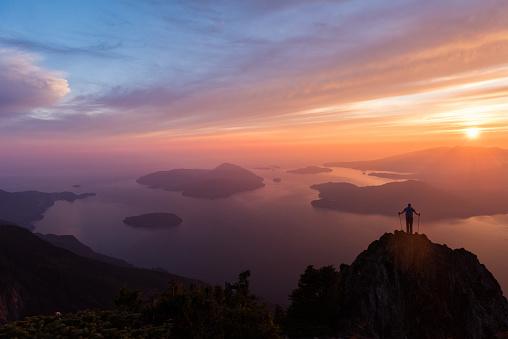 Hiker summiting a scenic peak at sunset