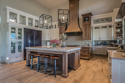 Oversized fridge, vent hood, and island make a bold statement in uniqely designed kitchen