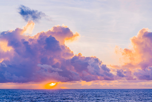 Stunning dramatic sunset or sunrise colorful sky cloud and oceas sea water wave nature background