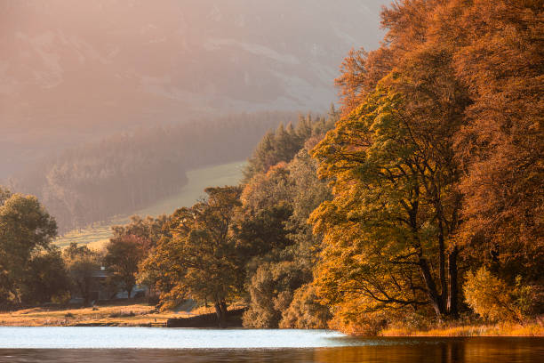 Stunning epic sunrise landscape image looking along Loweswater towards wonderful light on Grasmoor and Mellbreak mountains in Lkae District stock photo