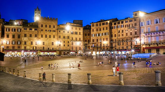 A stunning and suggestive evening view of Piazza del Campo in the historic heart of the medieval city of Siena, in Tuscany, central Italy. Center of the ancient medieval city since 1169, the Piazza del Campo or simply the Campo is one of the most beautiful and famous squares in the world for its particular shell shape. In this space every year the seventeen historical districts of Siena compete in the Palio, one of the oldest horse races in the world. In the background the white bell tower of the Cathedral or Duomo. Siena is one of the most beautiful Italian cities of art, in the heart of the Tuscan hills, visited for its immense artistic and historical heritage and for its famous popular traditions. Since 1995 the historic center of Siena has been declared a World Heritage Site by UNESCO. Image in high definition format.