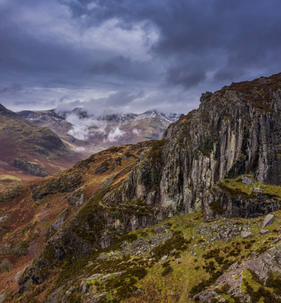 Stunning flying drone landscape image of Langdale pikes and valley in Winter with dramatic low level clouds and mist swirling around stock photo