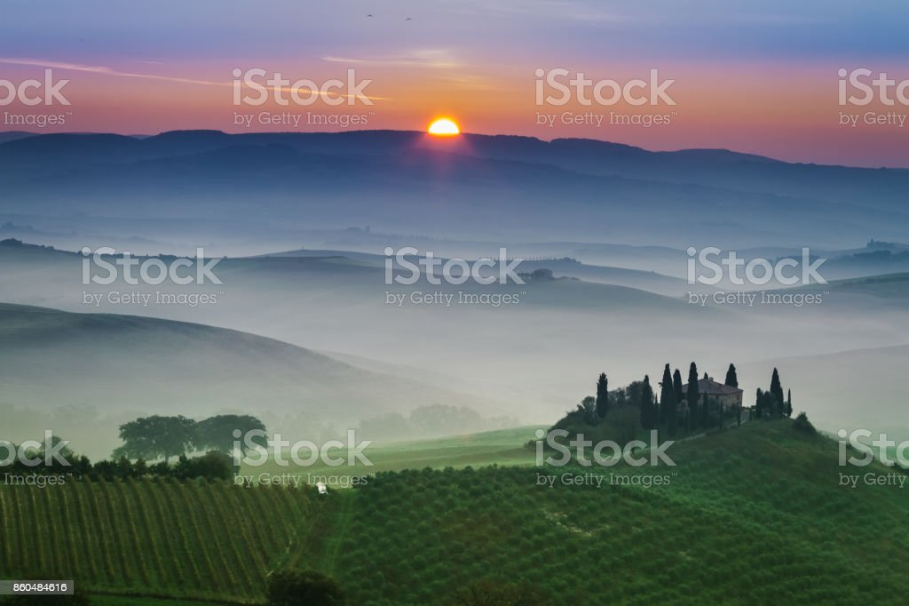 Stunning foggy green fields at sunset in Tuscany stock photo