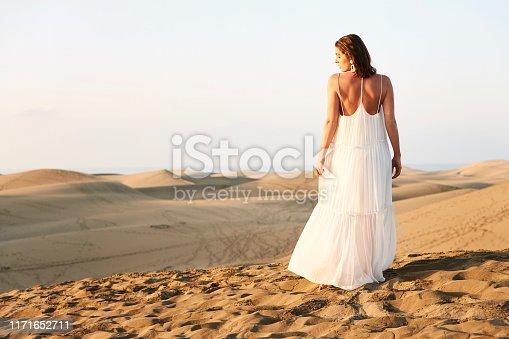 Stunning girl in white dress standing in sand dunes