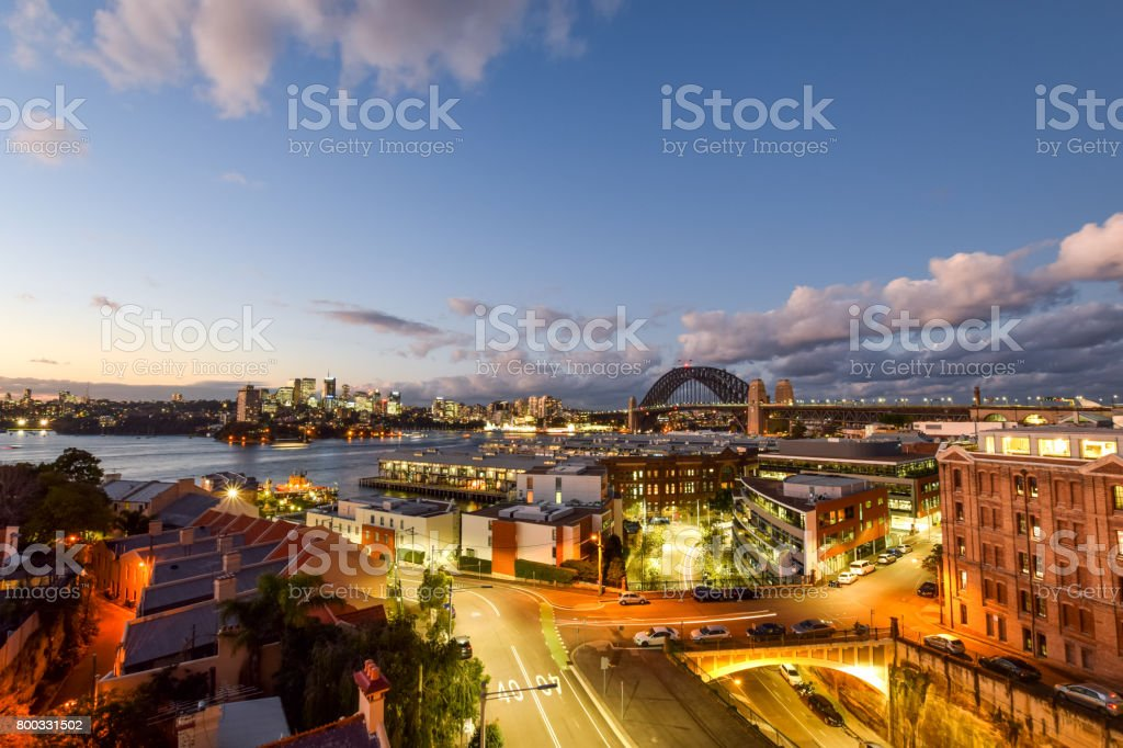 Stunning HDR night shot of the night skyline in Sydney, New South Wales, Australia. Beautiful view of the Sydney Harbour bridge, North Sydney, Millers Point and Walsh Bay. Shortly after sunset. stock photo