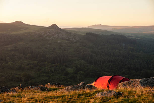 Stunning image of wild camping in English countryside during stunning Summer sunrise with warm glow of the sun lighting the landscape stock photo