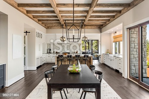 istock Stunning kitchen and dining room in new luxury home. Wood beams and elegant pendant lights accent this beautiful open-plan dining room and kitchen 950127464