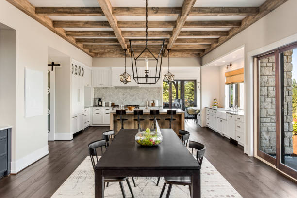 Stunning kitchen and dining room in new luxury home. Wood beams and elegant pendant lights accent this beautiful open-plan dining room and kitchen stock photo