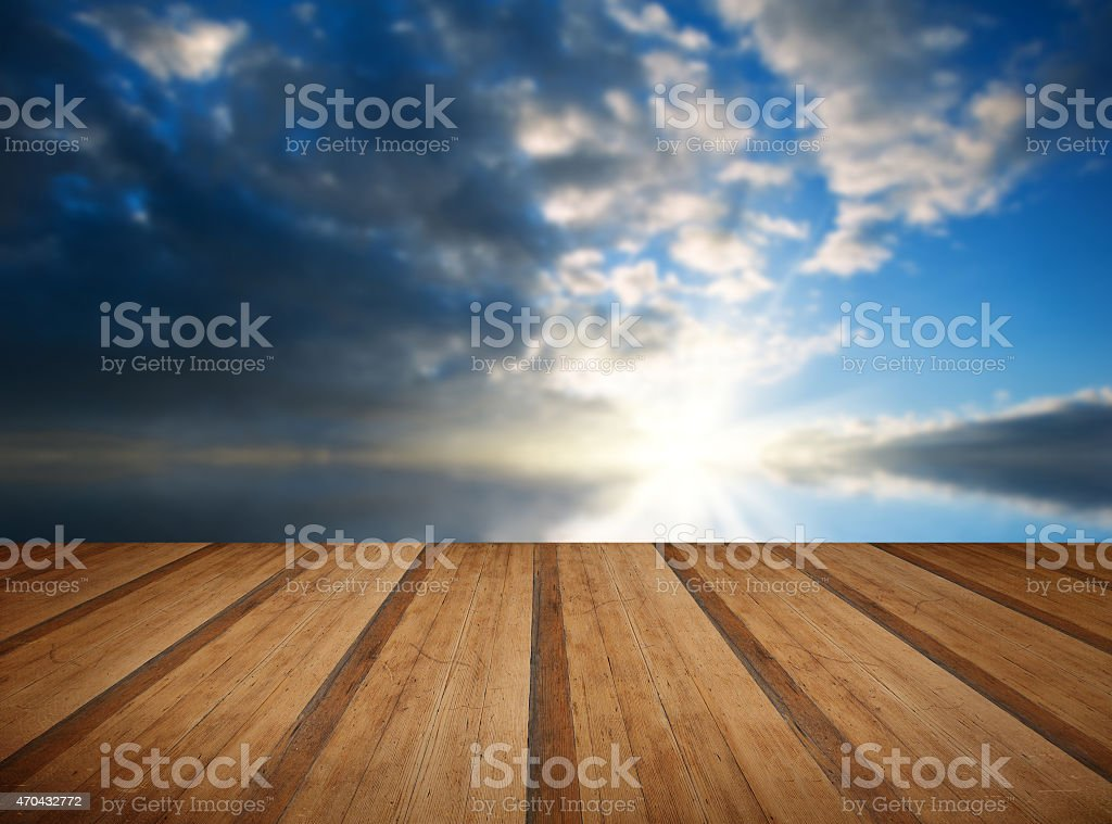 Stunning landscape at sunset reflected in ocean with wooden plan stock photo