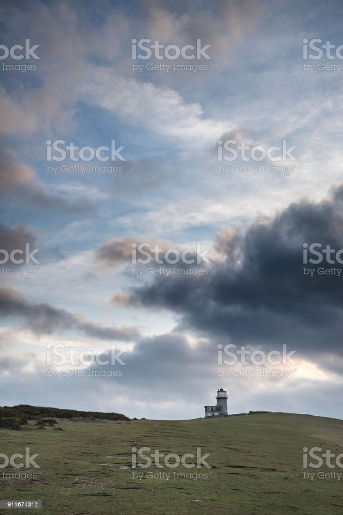 Stunning landscape image of Belle Tout lighthouse on South Downs National Park during stormy sky stock photo