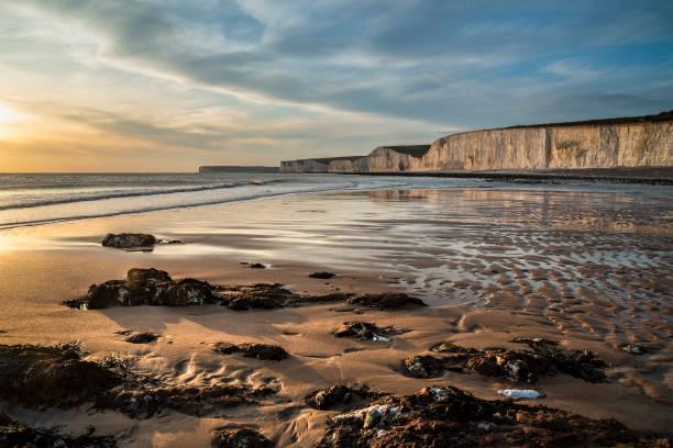 Stunning landscape image of white chalk cliffs with colorful vibrant sunset on English coast stock photo