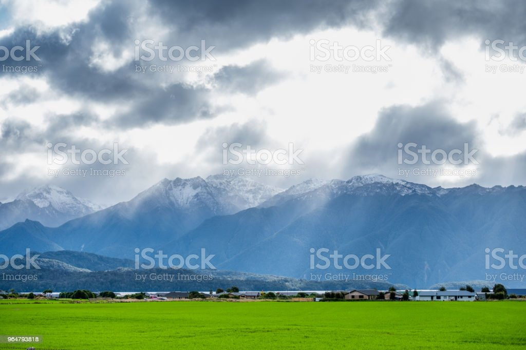 A stunning landscape scene of a rural area with green grassland cloudy snow mountain and sun rays after raining day. royalty-free stock photo