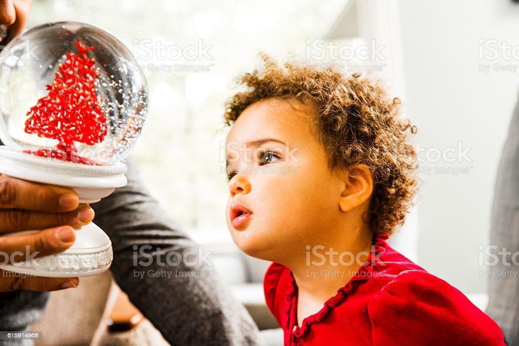 Stunning little Latina toddler looking a snow globe stock photo