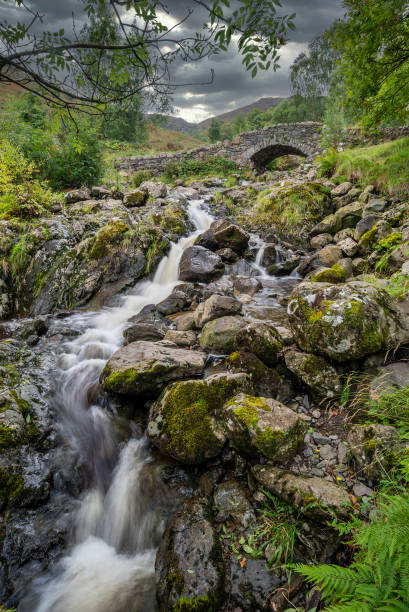 Stunning long exposure landscape image of Ashness Bridge in English Lake District during late Summer afternoon with dramatic lighting stock photo