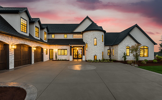 new luxury home with three car garage, large driveway and glowing exterior and interior lights