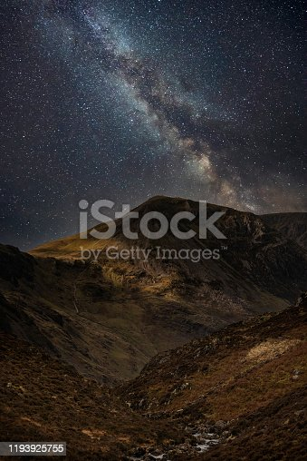 Beautiful epic digital composite landscape of Milky Way over Haystacks and High Stile in Lake District