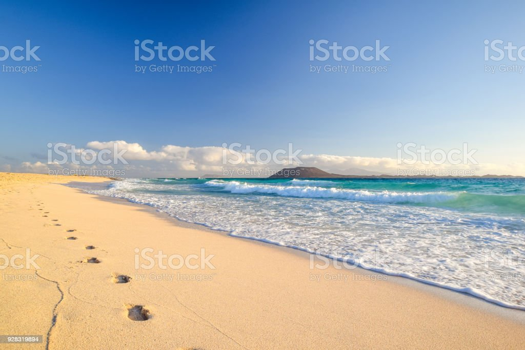 Stunning morning view of the islands of Lobos and Lanzarote seen from Corralejo Beach (Grandes Playas de Corralejo) on Fuerteventura, Canary Islands, Spain, Europe. Beautiful footprints in the sand. stock photo