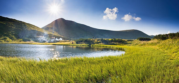 A stunning mountain lake with the sun beaming down