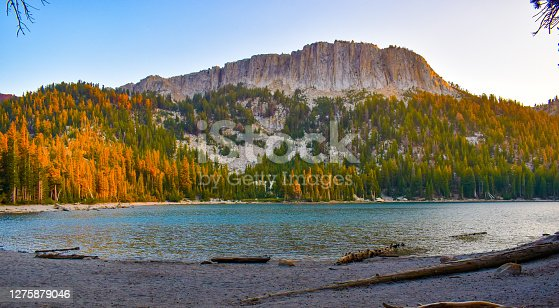 Stunning Autumn Fall landscape of mountain range towering over forest and turquoise colored alpine lake