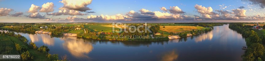 Stunning panoramic landscape with clouds reflected in tranquil river.