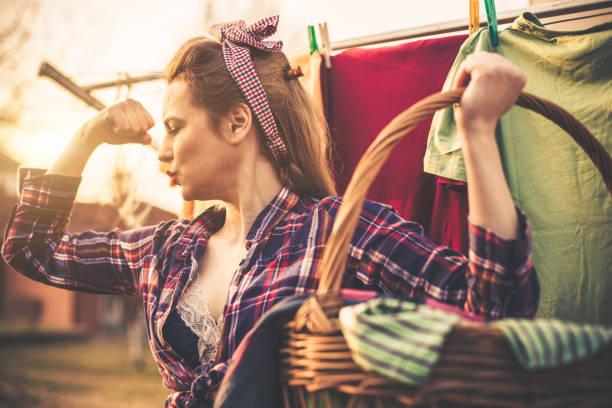 garota pin-up deslumbrante lavando roupa e carregando o cesto de roupa suja - dona de casa - fotografias e filmes do acervo