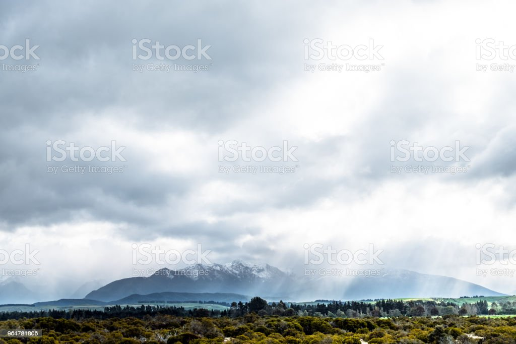 Stunning scene landscape during a cloudy day with sun ray through the cloud over the snow mountain. Dramatic photo style. royalty-free stock photo