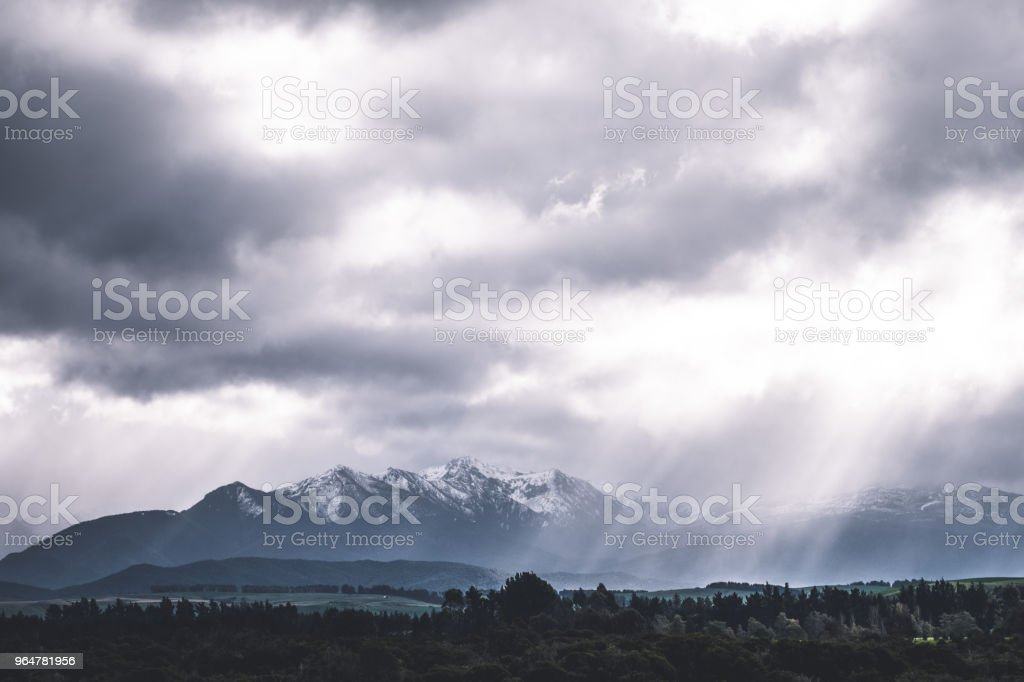 Stunning scene landscape during a cloudy day with sun ray through the cloud over the snow mountain. Dramatic photo style. stock photo