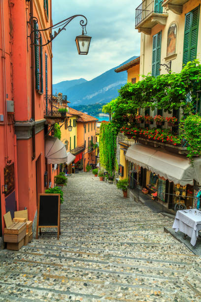 prachtige schilderachtige straat met kleurrijke huizen en bloemen in bellagio - como italië stockfoto's en -beelden