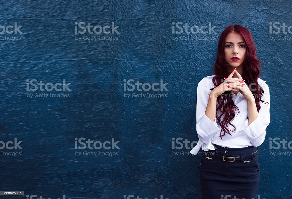 Stunning, seductive, serious, awesome girl with long curly red hair. - Photo