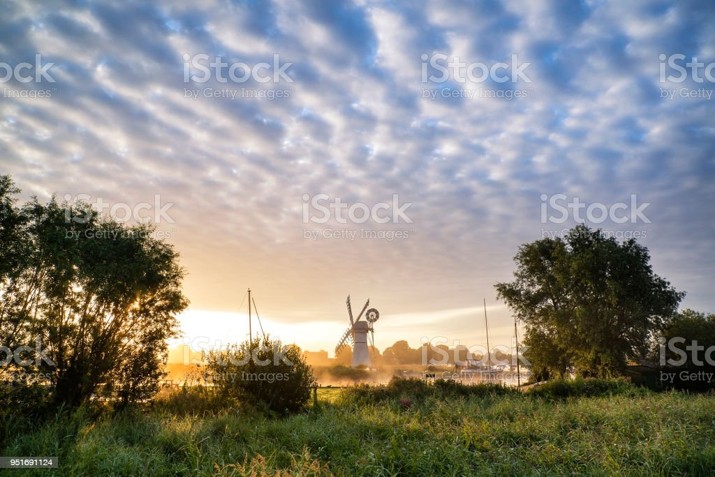 Stunning sunrise landscape over foggy River Thurne looking towards Thurne Mill Windmill stock photo