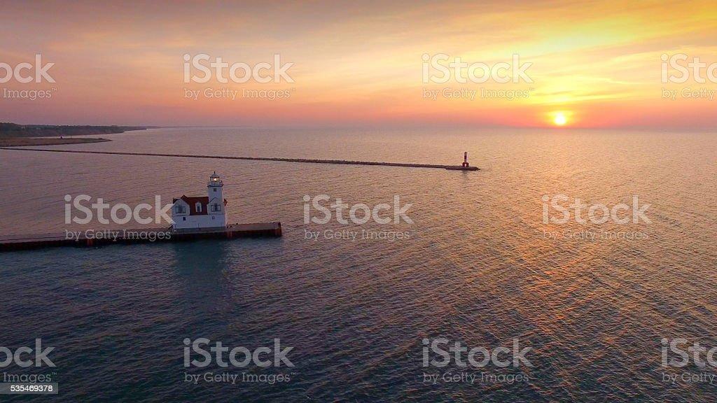 Stunning sunrise over illuminated lighthouse, Lake Michigan stock photo