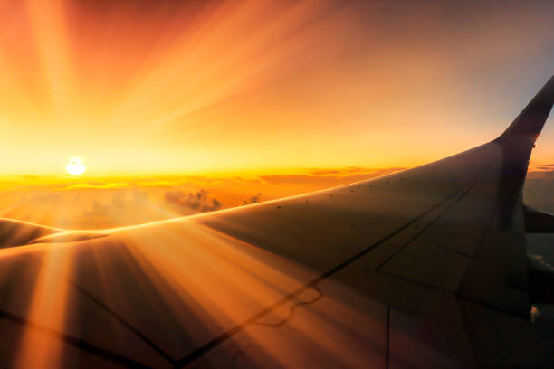 Stunning Sunrise Traveling Over Clouds On Plane With Sunbeams Over Wings Through Window stock photo