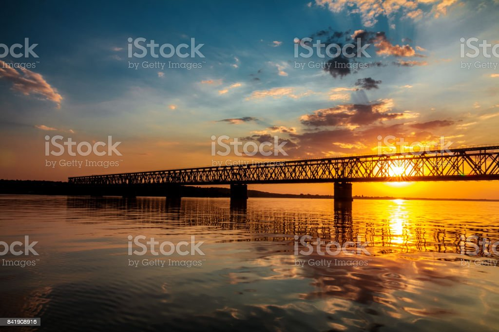 Stunning sunset colors over river with bridge in a summer evening royalty-free stock photo