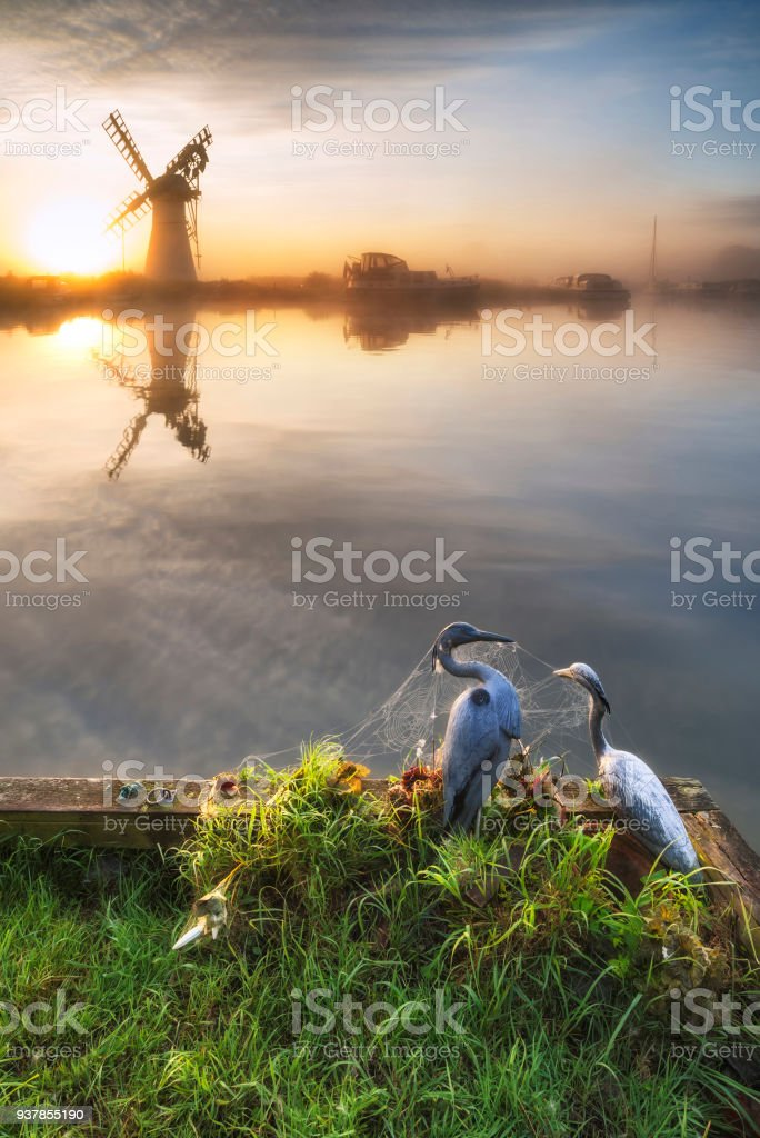 Stunning unrise landscape over foggy River Thurne looking towards Thurne Mill Windmill. stock photo