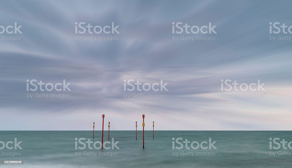 Stunning vibrant conceptual image of posts in sea standing senti stock photo