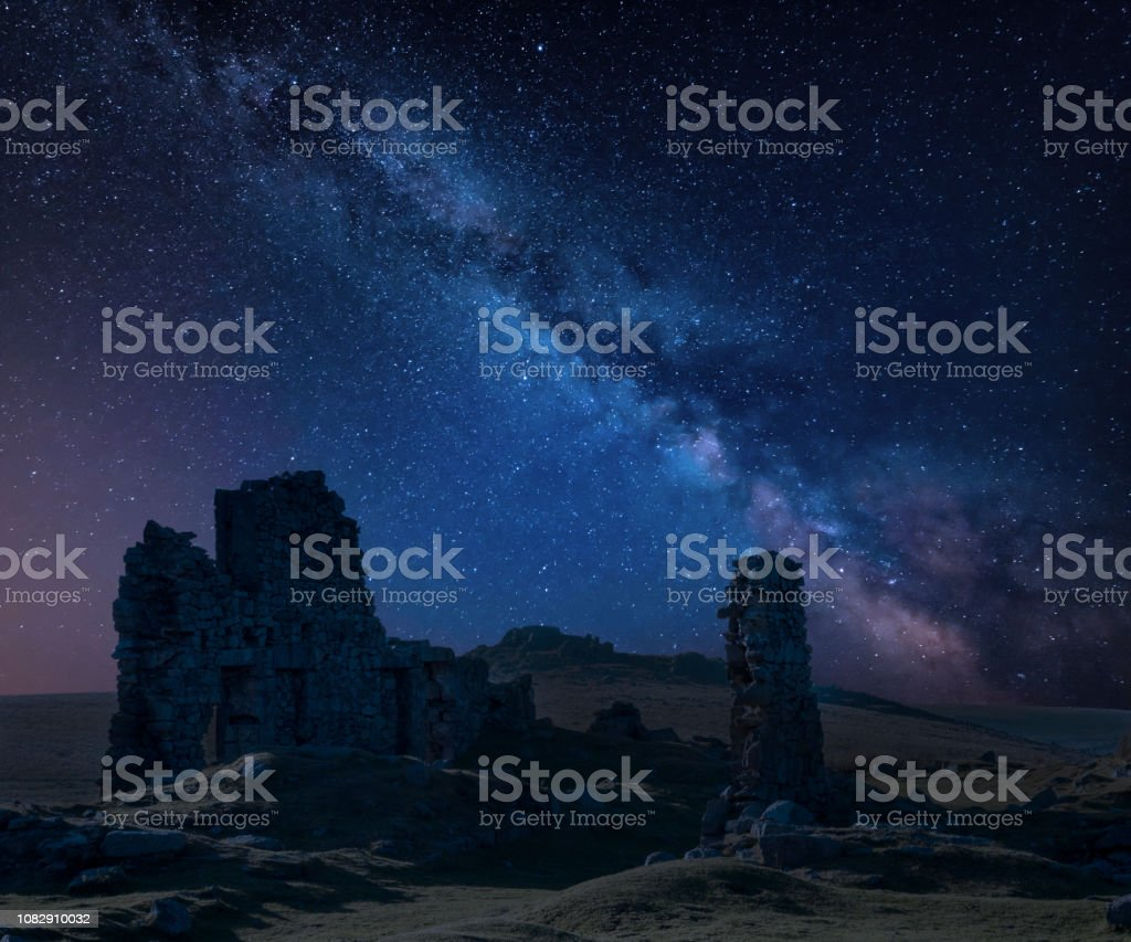 Stunning vibrant Milky Way composite image over abandoned Foggintor Quarry in Dartmoor with raking soft sunlight over ruins and derelict buildings stock photo