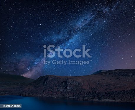 Stunning vibrant Milky Way composite landscape image over Catbells near Derwent Water in the Lake District towards Blencathra and Skiddaw peaks with lenticular clouds sitting above the peaks