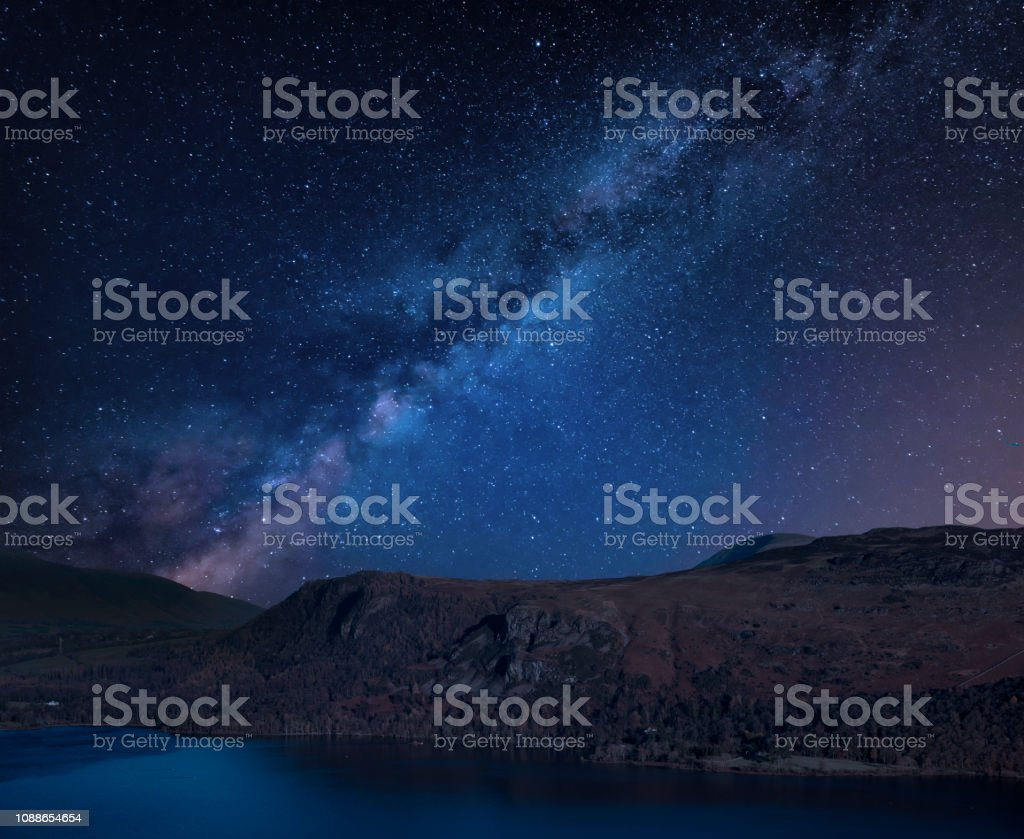 Stunning vibrant Milky Way composite image over Catbells near Derwent Water in the Lake District towards Blencathra and Skiddaw peaks with rare lenticular clouds sitting above the peaks stock photo