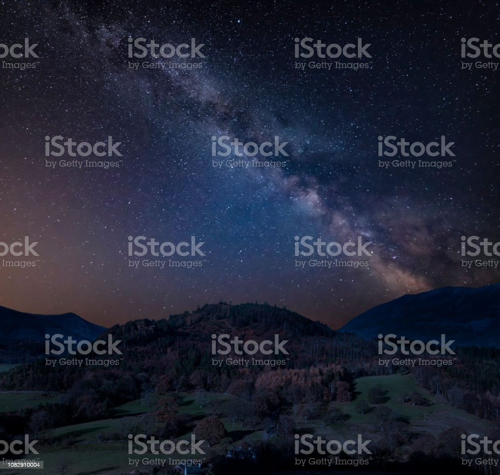 Stunning vibrant Milky Way composite image over Catbells near Derwentwater in the Lake District with vivid Fall colors all around the contryside scene stock photo