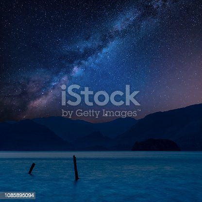 Stunning vibrant Milky Way composite landscape image over Derwent Water in Lake District during Autumn Fall sunrise with soft pastel colors