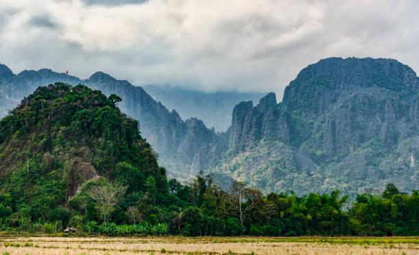 atemberaubender blick auf ein paar kalksteinberge, die von einigen sonnenstrahlen beleuchtet werden, die durch einige wolken filtern. vang vieng, laos. - vang vieng stock-fotos und bilder