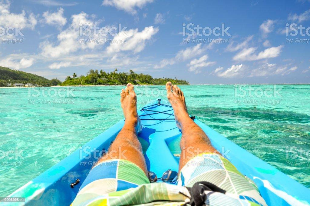 Stunning view of a young man's legs in a kayak near Motu Koromiri, a small island in the lagoon of Rarotonga near Muri Beach. Cook Islands in the South Pacific Ocean, Clear, shallow water, palm trees. stock photo