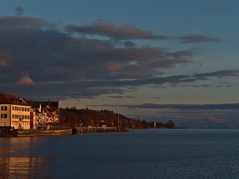 Meersburg, Germany - 12-26-2020: Stunning view of buildings and promenade on the shore of Lake Constance in the beautiful evening light in winter season with snow-capped mountains on the horizon.
