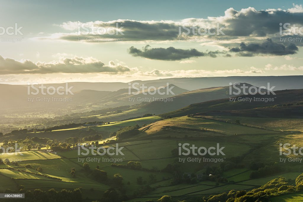 Stunning View Of Hope Valley From Stanage Edge. A photograph taken from Stanage Edge in the Peak District National Park, Derbyshire, UK. The photograph features a beautiful view of Hope Valley with dramatic light illuminating the landscape. Awe Stock Photo