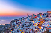 Stunning view of the village Oia on Santorini island at dusk with colorful twilight and white houses, windmill on the cliff, Greece.