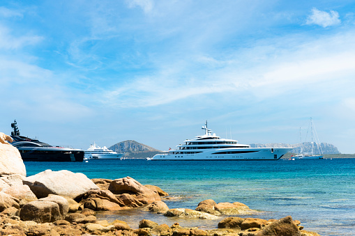 Sardinia, Italy, July 09, 2021. Stunning view of some luxury yachts sailing on a turquoise water during a sunny day. Cala di volpe bay, Costa Smeralda, Sardinia, Italy. Sardinia is the second largest island in the Mediterranean Sea.
