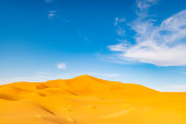 (Selective focus) Stunning view of some sand dunes illuminated during a sunny day in Merzouga, Morocco. Natural background with copy space.