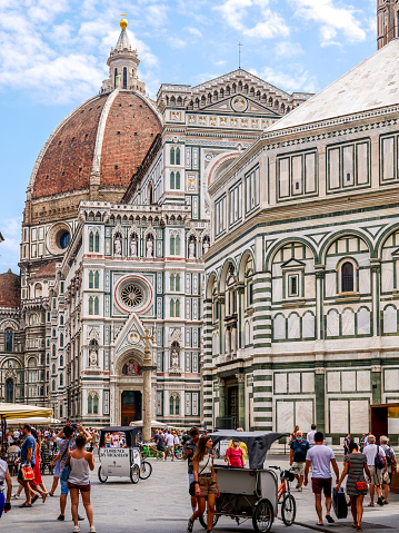 Florence, Tuscany, Italy, August 11 -- A stunning view of the facade of the Cathedral and the Baptistery of Santa Maria del Fiore, also known as the Duomo of Florence, and the majestic dome by Brunelleschi, in the historic heart of the Renaissance capital. The Duomo, visited every year by tens of thousands of tourists, is the third largest cathedral in Europe, after St. Peter in Rome and St. Paul in London. Built starting from 1296 on a project by Arnolfo di Cambio, the Florentine Cathedral was definitively finished and consecrated in 1436, after the completion of the majestic dome designed by Filippo Brunelleschi. Since 1982 the historic center of Florence has been declared a World Heritage Site by Unesco. Image in high definition format.