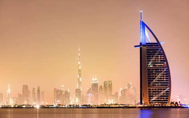 atemberaubender blick auf die beleuchtete skyline von dubai bei sonnenuntergang mit dem prächtigen burj khalifa im hintergrund und dem siebenklosternen luxushotel burj al arab im vordergrund. dubai, vereinigte arabische emirate. - jumeirah stock-fotos und bilder